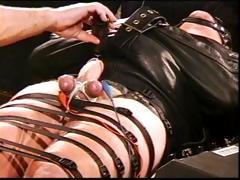 Totally bound hunk in leather straitjacket in CBT with high voltage stim to balls as he&#039;s jacked off